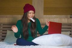 Young beautiful and happy Asian Chinese woman in winter hat sitting relaxed on bed holding credit card using laptop computer for stock photo