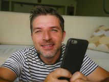 Lifestyle home portrait of young happy and attractive 30s man using internet dating app or messaging social media on mobile phone. Enjoying and smiling cheerful royalty free stock images