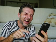 Lifestyle home portrait of young happy man laughing like crazy using mobile phone watching something funny on internet social. Lifestyle home portrait of young stock image