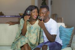 Lifestyle home portrait of young romantic and happy black Afro American couple in love drinking wine cup at living room couch stock photos