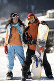 A lifestyle image of two young adult snowboarders stock images