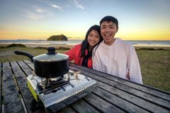 Lifestyle image of young happy asian couple eating hot pot stove on a table outdoor along beach. Leisure activity image of chinese royalty free stock image