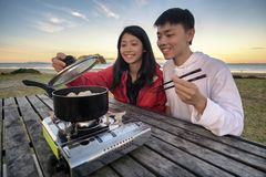 Lifestyle image of young happy asian couple eating hot pot stove on a table outdoor along beach. Leisure activity image of chinese stock photo