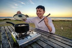 Lifestyle image of young happy asian man eating hot pot stove on a table outdoor along beach. Leisure activity image of chinese royalty free stock photo