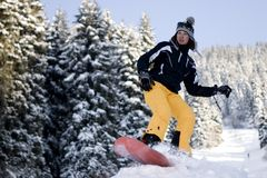 A lifestyle image of young snowboarder girl. A health lifestyle image of young adult  snowboarder girl jumping in winter forest in mountains Stock Images