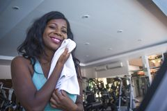 Lifestyle indoors portrait training at gym of young happy and attractive black afro American woman sweaty after hard exercise hold royalty free stock image