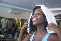 Lifestyle indoors portrait training at gym of young happy and attractive black afro American woman sweaty after hard workout holdi stock photos