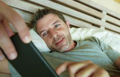 Lifestyle indoors portrait of young happy and attractive man at home bedroom using internet social media app networking from bed s royalty free stock photo