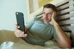 Lifestyle indoors portrait of young happy and attractive man at home bedroom using internet social media app networking from bed t stock photography