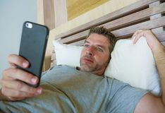 Lifestyle indoors portrait of young happy and attractive man at home bedroom using internet social media app networking from bed t stock photos