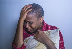 Lifestyle indoors portrait of young sad and depressed black afro American woman sitting at home floor feeling desperate and worrie. Lifestyle indoors shady royalty free stock photography