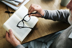 Lifestyle Living Recreation Relaxation Leisure Concept. Senior adult need glasses to read a book stock image