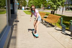 Happy teenage girl in shades riding on longboard. Lifestyle, longboarding and people concept - smiling young woman or teenage girl in sunglasses riding on Stock Image