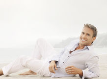Lifestyle male model with smile. Bright outdoor fashion lifestyle portrait of a great looking young male model with nice happy smile lying down in classic casual Royalty Free Stock Image