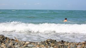 Lifestyle man walks into the sea on a pebble beach and swims on the wave. stock video