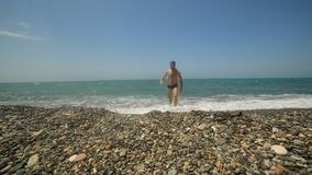 Lifestyle man walks into the sea on a pebble beach and swims on the wave. stock footage