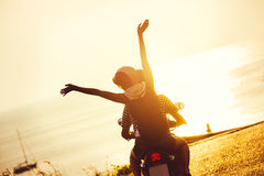 Lifestyle motorcycle couple travel sunset sea. Lifestyle photo of happy couple on motorcycle traveling to the sea at sunset time Stock Photos