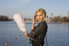 lifestyle Mujer feliz joven del inconformista que come el caramelo de algodón azucarado, vista asombrosa de la ciudad del puente Foto de archivo