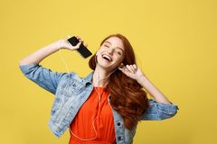 Lifestyle and Music Concept: Beautiful young curly red hair woman in headphones listening to music and dancing on vivid. Yellow background Royalty Free Stock Photos