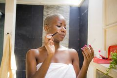 Lifestyle natural portrait of young attractive and happy black african American woman at home bathroom applying face makeup with b. Rush looking at toilet mirror stock photos
