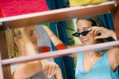 Lifestyle natural portrait of young beautiful and happy girlfriends trying on sunglasses shopping cheerful at cool vintage beauty royalty free stock photography
