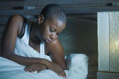 Lifestyle night portrait of young sad and stressed black african American woman lying on bed upset trying to sleep suffering insom. Nia and depression feeling stock photo