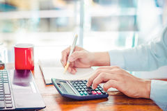The lifestyle of office workers. Young businessman using calculator for finance and tax. Businessmen working at modern business office and writing on note Royalty Free Stock Photos