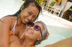 Lifestyle outdoors portrait of Asian girlfriends enjoying Summer holidays at tropical beach resort swimming pool taking selfie royalty free stock photo