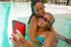 Lifestyle outdoors portrait of Asian girlfriends enjoying Summer holidays at tropical beach resort swimming pool taking selfie stock photo