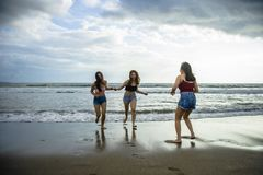 Happy and excited young Asian Chinese women enjoying having fun on beautiful sunset beach in girlfriends summer holidays trip toge stock image
