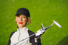 Lifestyle outdoors portrait of young beautiful and happy woman at playing golf holding ball and putter club smiling cheerful in st stock images
