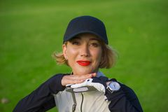 Lifestyle outdoors portrait of young beautiful and happy woman at playing golf leaning sweet on club smiling cheerful in stylish g stock photography