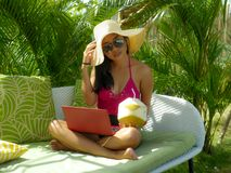 Lifestyle outdoors portrait of young happy and attractive Asian Indonesian teenager girl in bikini and hat working with laptop stock photo