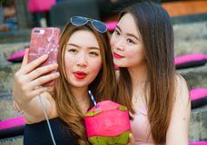 Lifestyle outdoors portrait of young happy and beautiful Asian Chinese girls taking selfie picture with mobile phone enjoying holi royalty free stock photography