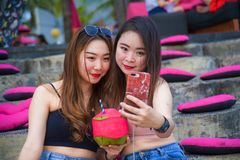 Lifestyle outdoors portrait of young happy and beautiful Asian Chinese girls taking selfie picture with mobile phone enjoying holi. Days trip together sitting at stock photo