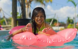 Lifestyle outdoors portrait of young happy and cute female child having fun with inflatable airbed in holidays resort swimming. Pool smiling carefree and royalty free stock photo