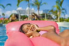 Lifestyle outdoors portrait of young happy and cute female child having fun with inflatable airbed in holidays resort swimming. Pool smiling carefree and stock image