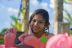 Lifestyle outdoors portrait of young happy and cute female child having fun with inflatable airbed in holidays resort swimming. Pool smiling carefree and stock images