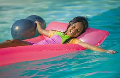 Lifestyle outdoors portrait of young happy and cute female child having fun with inflatable airbed in holidays resort swimming. Pool smiling carefree and royalty free stock image