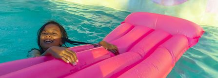Lifestyle outdoors portrait of young happy and cute female child having fun with inflatable airbed in holidays resort swimming. Pool smiling carefree and royalty free stock photos