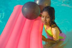 Lifestyle outdoors portrait of young happy and cute female child having fun with inflatable airbed in holidays resort swimming. Pool smiling carefree and stock photo