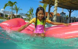 Lifestyle outdoors portrait of young happy and cute female child having fun with inflatable airbed in holidays resort swimming. Pool smiling carefree and stock photography