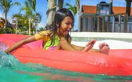 Lifestyle outdoors portrait of young happy and cute female child having fun with inflatable airbed in holidays resort swimming. Pool smiling carefree and stock photos