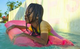 Lifestyle outdoors portrait of young happy and cute female child having fun with inflatable airbed in holidays resort swimming. Pool smiling carefree and royalty free stock photography