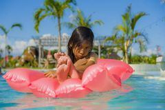 Lifestyle outdoors portrait of young sweet and gorgeous female child having fun lying on inflatable airbed in holidays resort. Swimming pool with wet hair and stock photos