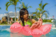 Lifestyle outdoors portrait of young sweet and gorgeous female child having fun lying on inflatable airbed in holidays resort. Swimming pool with wet hair and stock images