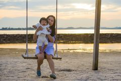Young sweet and happy Asian Chinese woman holding baby girl swinging together at beach swing on Summer sunset in mother and little stock photos