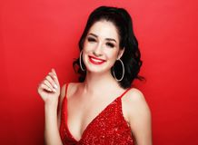 Free Lifestyle, Party And People Concept - Gorgeous Brunette Woman In An Evening Dress Flirty And Playful On A Red Background Royalty Free Stock Photo - 160502225