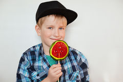 Lifestyle and people concept. Adorable little male child with blue eyes and fair hair in black cap and checked shirt posing with c Stock Photo