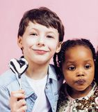 Lifestyle people concept: diverse nation children playing togeth. Er, caucasian boy with african little girl holding candy happy smiling close up Stock Images